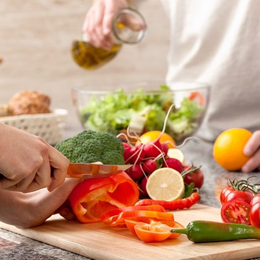 Cutting a vegetables for a salad with an olive oil